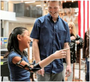 Glückliche Frau mit Armprothese lacht und freut sich mit LaChappelle im Hintergrund