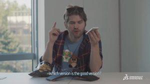 """Männliche Person sitzt am Tisch mit Smartphone in der Hand, Untertitel: """"Welche Version ist die richtige Version?"""""""