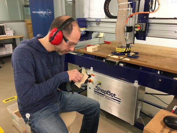 Sal working on the Cubie bases next to the CNC machine