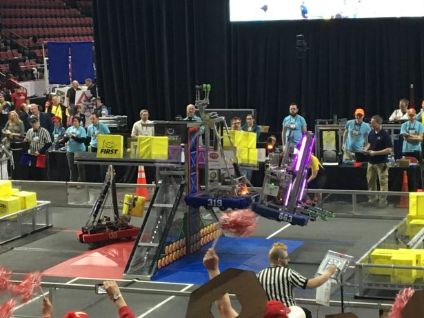 Two bots lift up the POWER UP scale to fight the boss at the FIRST New England District Championship