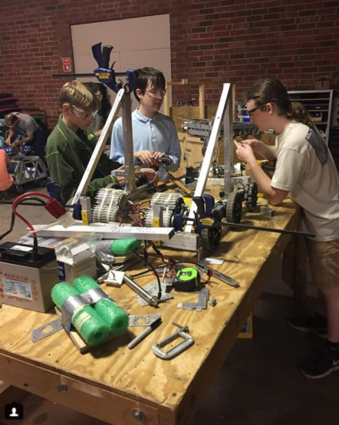 A YETI team member helping a rookie team build their bot.