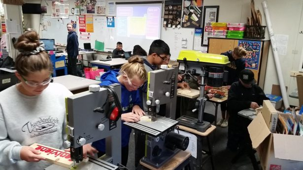 Jackie's students using power tools.
