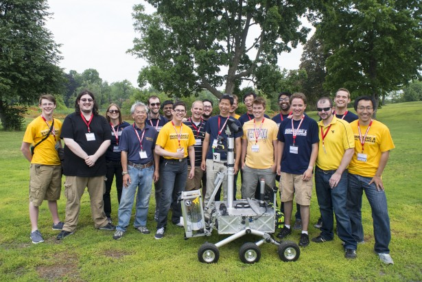 Members of the Mountaineers team from West Virginia University pose for a picture with their robot after successfully recovering two samples during their attempt at the level two challenge during the 2015 Sample Return Robot Challenge, Thursday, June 11, 2015 at the Worcester Polytechnic Institute (WPI) in Worcester, Mass.  Sixteen teams are competing for a $1.5 million NASA prize purse. Teams will be required to demonstrate autonomous robots that can locate and collect samples from a wide and varied terrain, operating without human control. The objective of this NASA-WPI Centennial Challenge is to encourage innovations in autonomous navigation and robotics technologies. Innovations stemming from the challenge may improve NASA's capability to explore a variety of destinations in space, as well as enhance the nation's robotic technology for use in industries and applications on Earth.  Photo Credit: (NASA/Joel Kowsky)